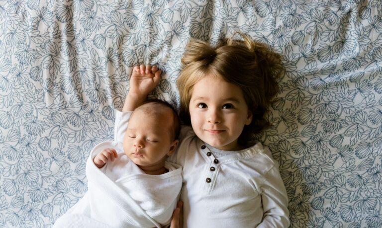 Dziewczynka i malutkie dziecko leżą na łóżku