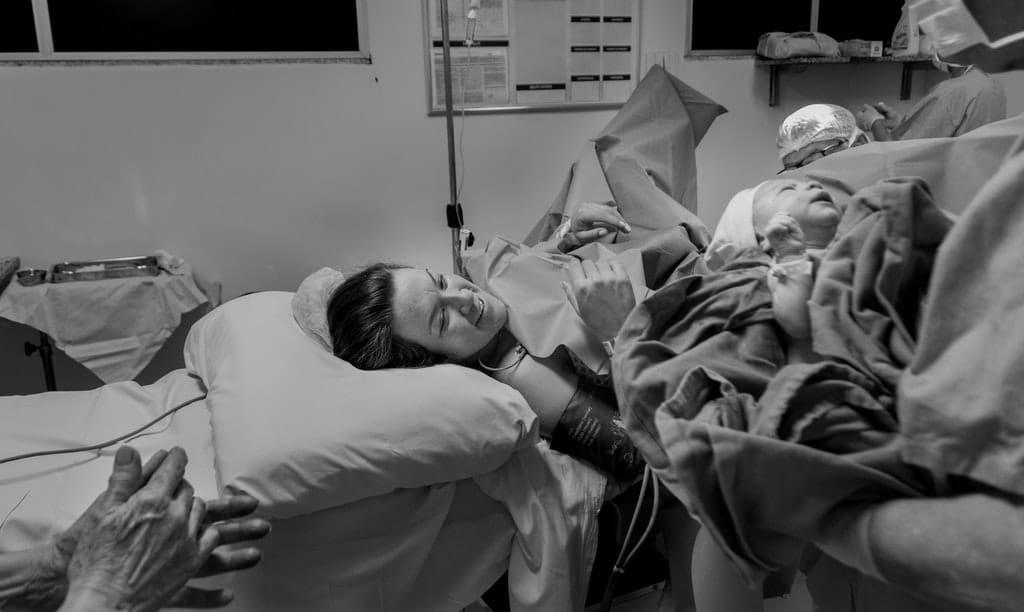Radosna kobieta tuż po porodzie, dziecko trzymane przez lekarza owinięte kocem