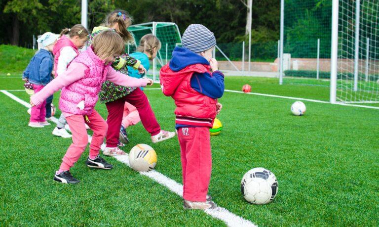 dzieci z piłkami na boisku